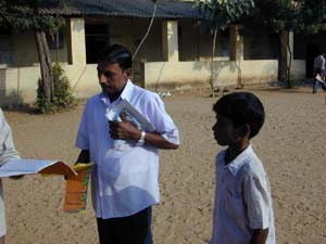 Raghu's teacher congratulates him on achieving 1st Rank (1st in the class)
