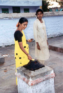 Selvi and Lakshmi make an offering at the village temple.