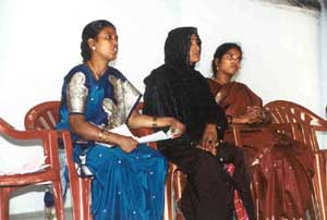 Committee members speak at a monthly meeting for Women's Self Help Groups.